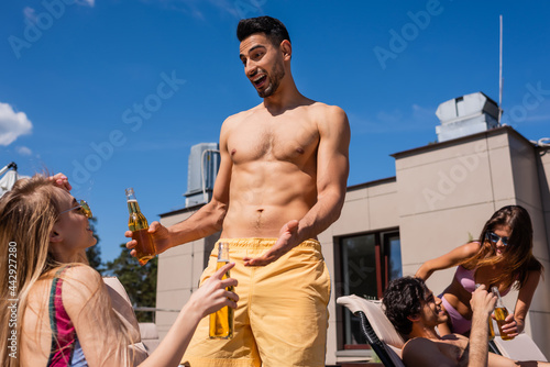 Obraz na plátně Positive muslim man with beer talking to friend in swimwear outdoors