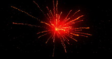 Glowing Red Firework Exploding On Black Background With Defocussed Blue Spots