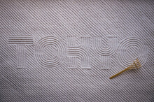 Japanese Zen Garden Raked With The Word TOKYO In Capital Letters In Textured White Sand With Diagonal Stripe Pattern And Rake