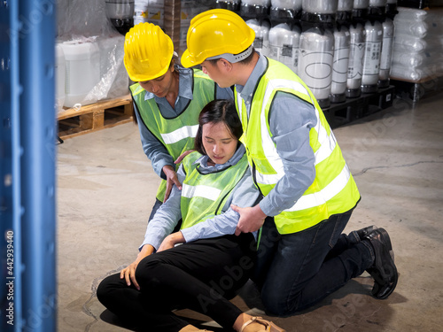 Fototapeta Two male and female colleagues are rescuing a female worker who is fainted from working inside a warehouse
