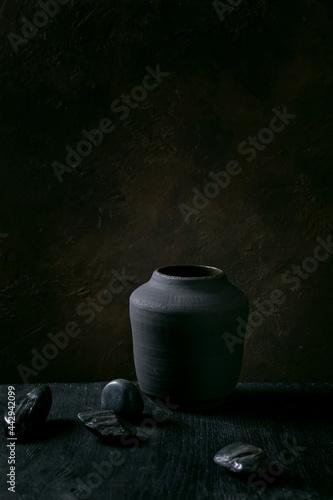 Billede på lærred Black ceramic vase on black wooden table