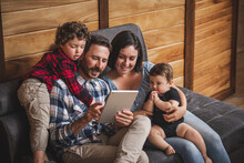 Cheerful Family Using Tablet Together At Home