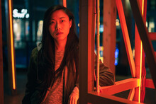 Portrait Of Asian Girl Posing Near To Red Neon Light On The Street