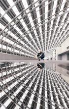 Unrecognizable Man Hunkering Down In Futuristic Passage