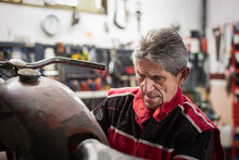Repairman Fixing Old Broken Motorcycle In Workshop