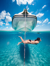 Half Underwater  Of Young Girl Swimming On A Turquoise Sandy Sea, In Front Of The Bow Of A Dinghy.