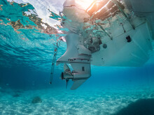 Underwater View Of A Outboard Engine Stern On A Dinghy Immersed In A Turquoise Sea.