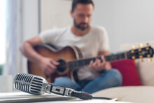 Anonymous Man Playing Guitar On Couch Near Table With Retro Mic