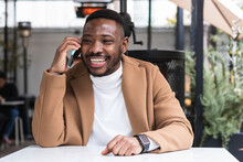 Content Black Man Speaking On Smartphone In Cafe