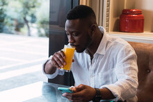 Black Man Browsing On Phone In Cafe While Sipping An Orange Juice