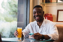 Happy Black Man Using Smartphone In Cafe While Sipping An Orange Juice