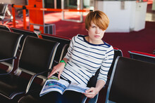 Woman Reading Newspaper At Charles De Gaulle Airport,