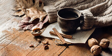 Hot Steaming Coffee, Cinnamon, Nuts And A Warm Sweater On A Wooden Table Background. Seasonal, Morning Coffee, Sunday Relaxation And Still Life Concept.