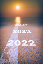 New Year 2022 To 2024 On Asphalt Road Surface With White Marking Line Leading Into Abstract Blur Sunlight And Sun. Start To Sustainable Business Strategy Concept