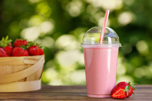 Strawberry Smoothie In Disposable Plastic Glass On Wooden Table