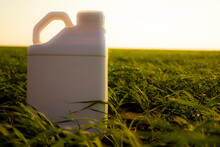 White Canister Against The Background Of Agriculture, Canisters From Under Different Types Of Chemical Products.