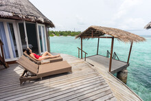 Woman Lying On Deckchair Relaxing In Resort