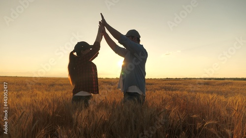 Canvas Print Happy business people, farmer, man and woman, greet each other with their hands in a wheat field