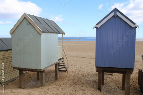Fotografie, Tablou Beach landscape showing rear view of wood painted beach huts on beautiful sandy
