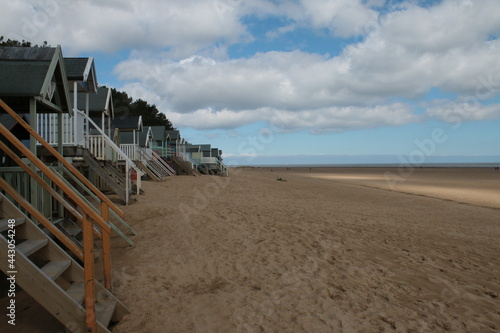 Beach landscape showing wide view of wood painted beach huts on beautiful sandy Fototapet