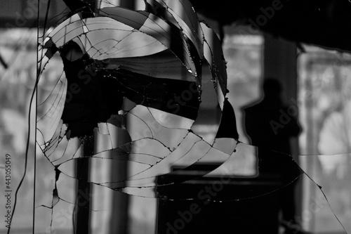 Foto silhouette du reflet d'un photographe dans une vitre cassé dans un magasin aband