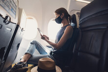 Woman Traveling During Pandemic Wearing Face Mask. Young Woman Passenger In Airplane Using Smartphone. Health Care, Coronavirus Covid-19 Protection, Vacations, Travel, Technology, Lifestyle Concept
