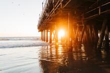 Golden Sunset Light Through Pier Piles