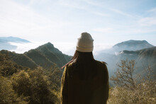 Female Traveler Admiring View Of Mountains Among White Fluffy Clouds And Thick Mist In Sunny Day