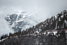 Forest On A Snow-covered Mountain Partially Hidden By Clouds