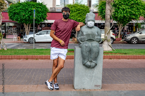 Fototapeta A male tourist wearing a medical face mask poses near a stone sculpture of a masked accordionist on Ataturk Boulevard in Alanya, Turkey