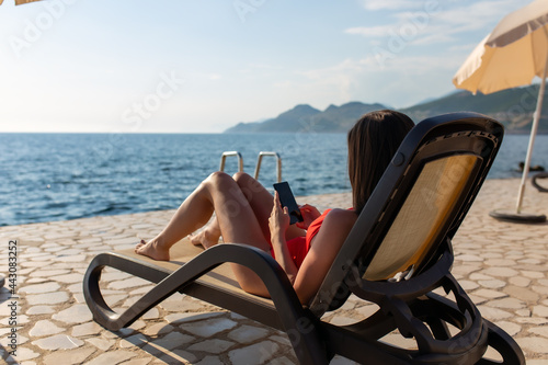 Beautiful young woman relaxing on beach chair and using mobile phone Poster Mural XXL