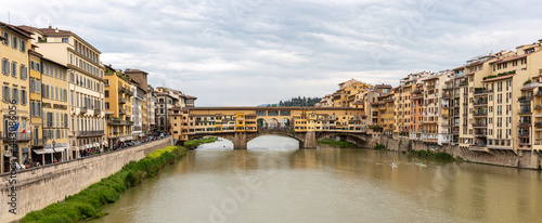 Ponte Vecchio, old bridge on the river in Florence with dramatic sky