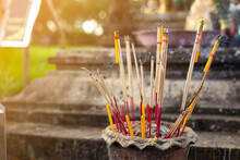 Burning Incense Sticks In A Buddhist Temple And Orange Light