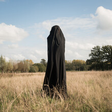 Woman In A Field Covered By Black Thin Fabric Expressing Feelings And Emotions
