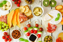 Italian Theme Grazing Table Scene Against A White Wood Background. Selection Of Cheese, Meat And Fruit Appetizers. Overhead View.