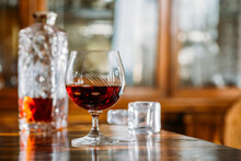 Cognac Glass On Wooden Table With Natural Light