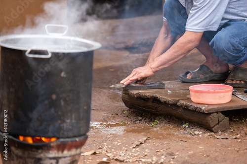 Fotografie, Obraz selective focus, hands of rural villagers man raining knife And set up a stove to bring the animals in the farm to make food to eat with family and friends