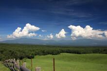 北軽井沢の夏。浅間牧場の風景。放牧場の向こうに見える信州の山と、白い雲、青い空。