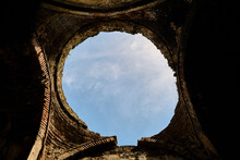 Old Turkish Bath Ruins In Iznik. It Is Established By Ottoman Empire Period Made Of Red Bricks Wall And Currently It Is Abandoned And Brownfield With Demolished Ist Dome And Sky Is Observed.