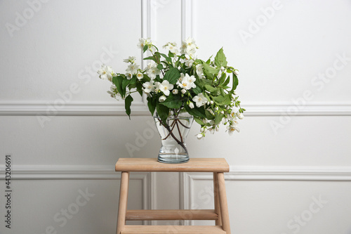 Obraz na plátně Beautiful bouquet with fresh jasmine flowers in vase on wooden table indoors