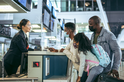 Fotomural Ground staff assisting family at checkin counter during pandemic