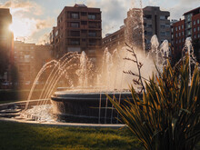 Incredible Sunset Filtering Between The Buildings Of A Park In Valencia. The Sun's Rays Illuminate A Fountain And Tint A Park With Warm Color.