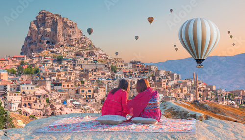 Fotografie, Obraz Hot air balloon flying over spectacular Cappadocia - Japanese girls watching hot