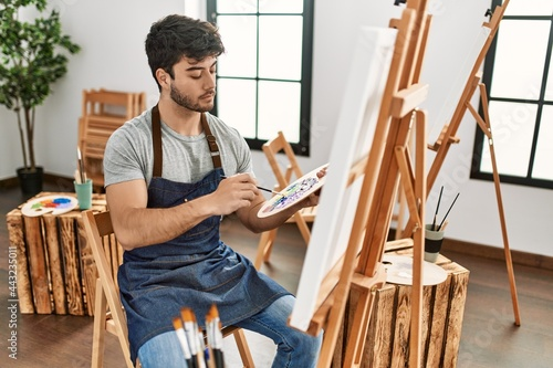 Fotografiet Young hispanic artist man concentrated painting at art studio