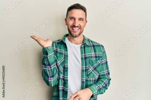 Handsome man with beard wearing casual clothes smiling cheerful presenting and pointing with palm of hand looking at the camera Fotobehang