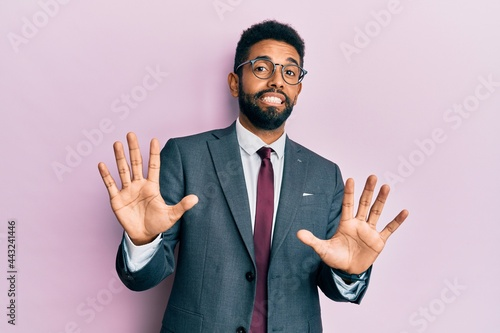 Tela Handsome hispanic business man with beard wearing business suit and tie afraid and terrified with fear expression stop gesture with hands, shouting in shock