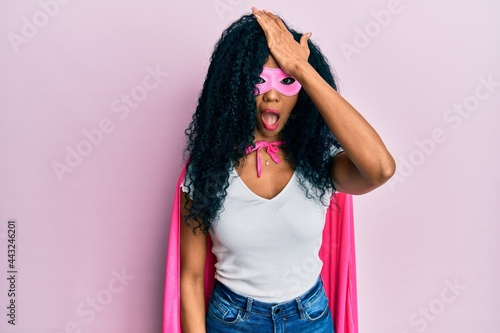 Foto Middle age african american woman wearing super hero costume surprised with hand on head for mistake, remember error