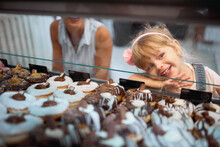Mother And Daughter Buying Mouth-watering Donuts Together