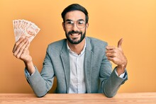 Young Hispanic Man Holding Turkish Lira Banknotes Sitting On The Table Smiling Happy And Positive, Thumb Up Doing Excellent And Approval Sign