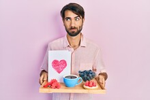 Young Hispanic Man Holding Tray With Breakfast Food And Heart Draw Smiling Looking To The Side And Staring Away Thinking.